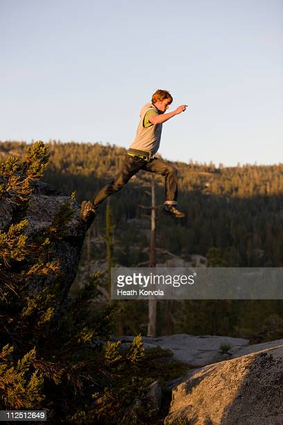 man jumping off high rock in mountains. - newhealth stock photos and pictures