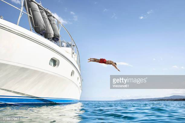 Man jumping off his motor yacht