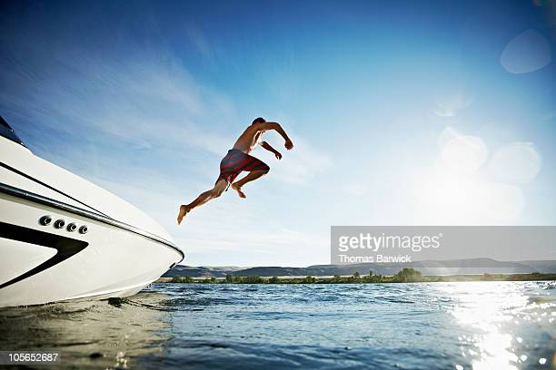 Man jumping off of ski boat into water