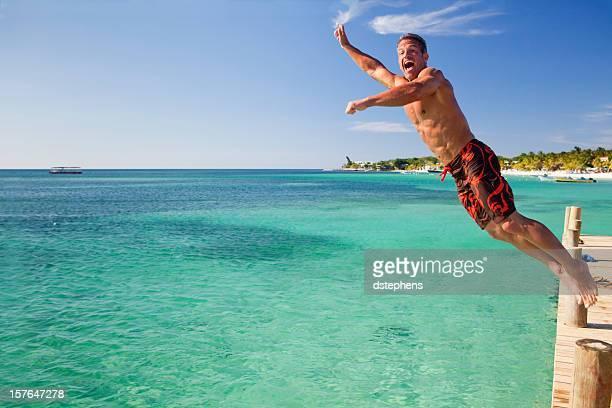 Man jumping off pier into sea
