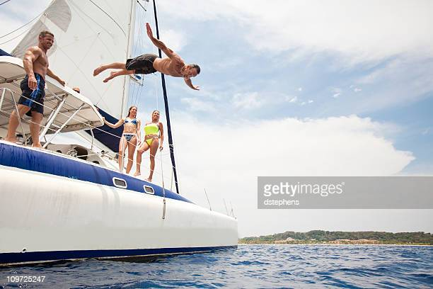 man jumping off sailboat into caribbean sea - catamaran stock photos and pictures