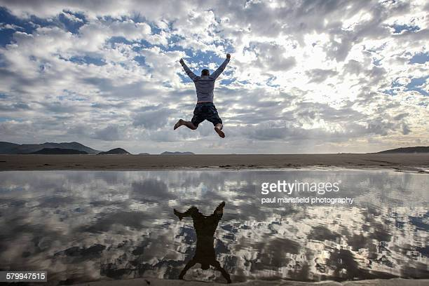 man jumping on beach - leap of faith stock photos and pictures