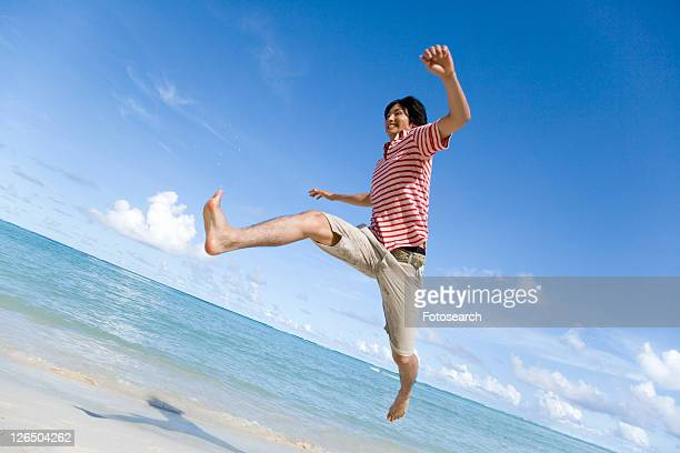 Man jumping on beach, Saipan, USA