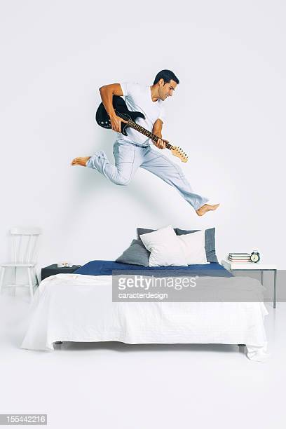 Man jumping on bed playing electric guitar