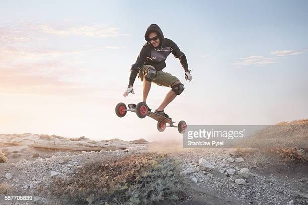 man jumping on landboard at sunrise - only mid adult men stock pictures, royalty-free photos & images