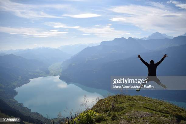 Man Jumping On Mountains Against Sky