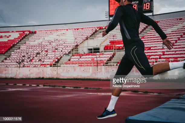 man jumping on rainy day - men's field event stock pictures, royalty-free photos & images