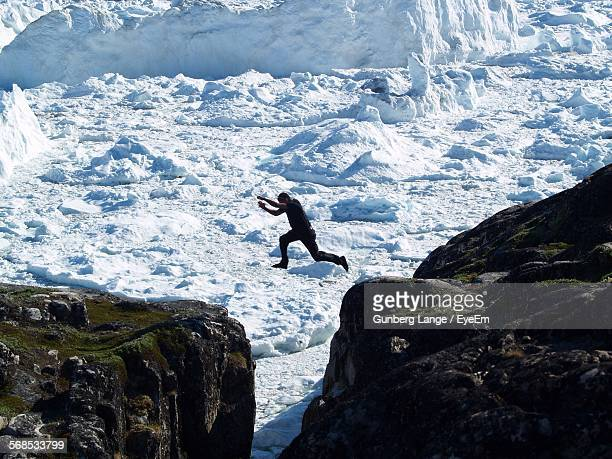 Man Jumping On Rock Formations In Front Of Snow Landscape