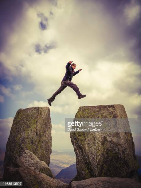 man jumping on rocks against sky during sunset - david cliff stock pictures, royalty-free photos & images