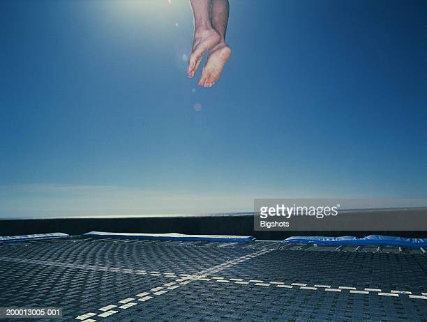 Man jumping on trampoline, low section