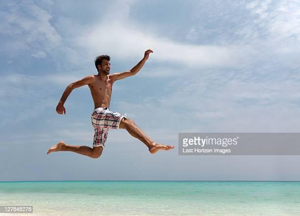 Man jumping on tropical beach