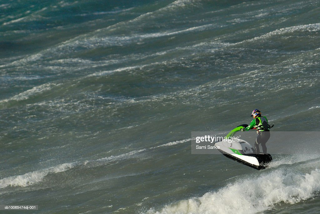 Man jumping on waves with jet-ski, elevated view : Stock Photo