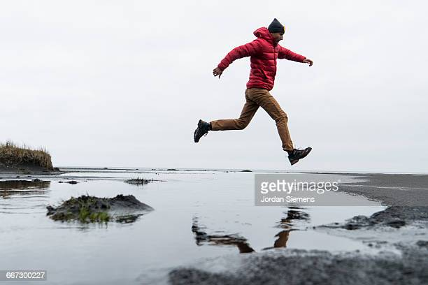 A man jumping over a small creek