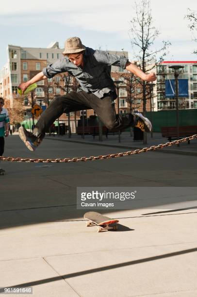 Man jumping over chain fence on sunny day