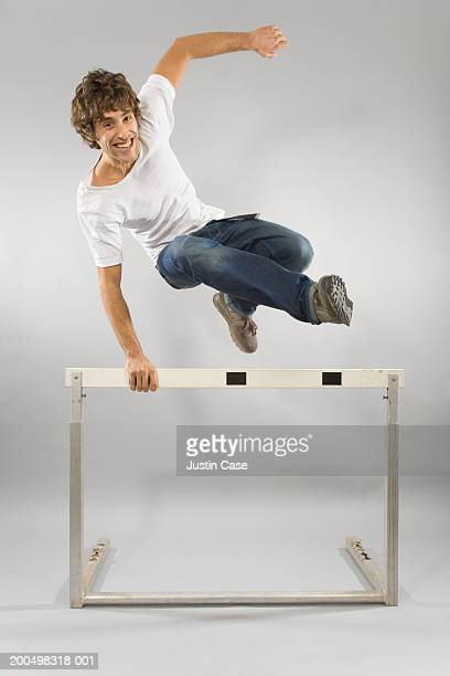 Man jumping over hurdle, indoors