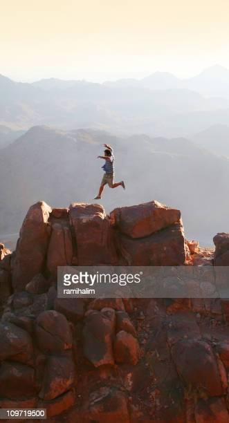 man jumping over mountain peak