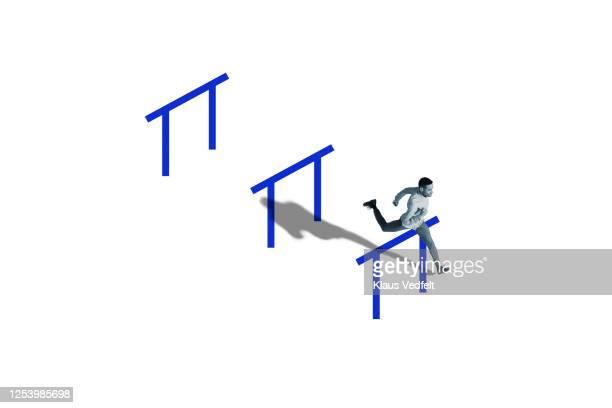 man jumping over obstacle while running in race - sprint sport wettbewerbsform stock-fotos und bilder