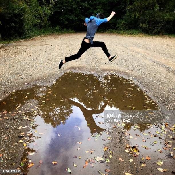 man jumping over puddle on dirt road - lynn pleasant stock pictures, royalty-free photos & images