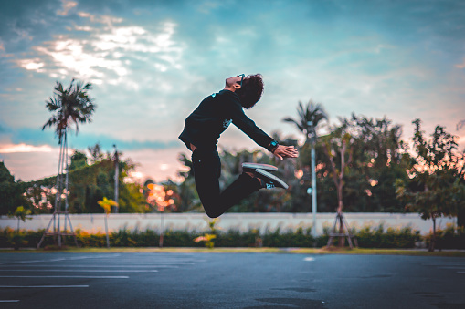 Man Jumping Over Road Against Sky During Sunset - gettyimageskorea