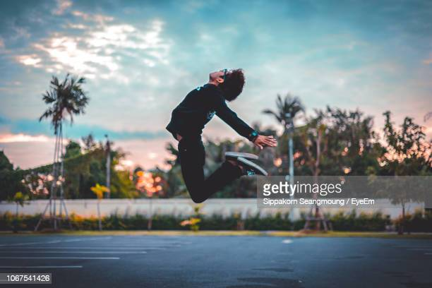 Man Jumping Over Road Against Sky During Sunset