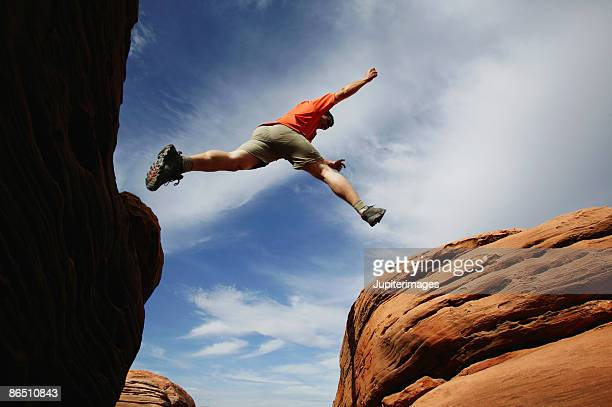 Man jumping over rock ledge