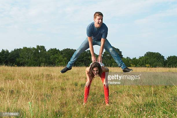 Man jumping over the top of woman