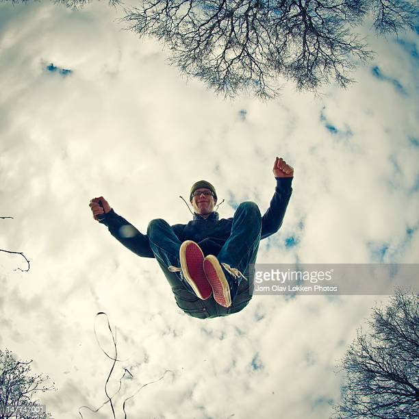 man jumping - directly below stock pictures, royalty-free photos & images