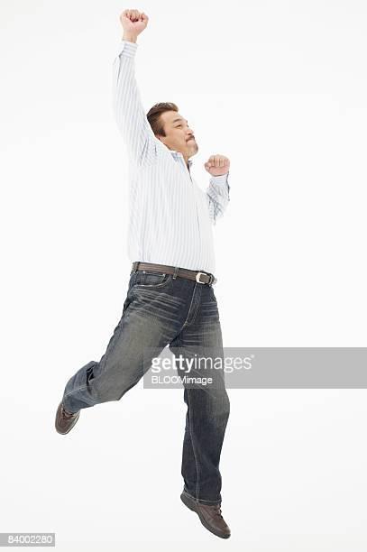 Man jumping raising fist, studio shot