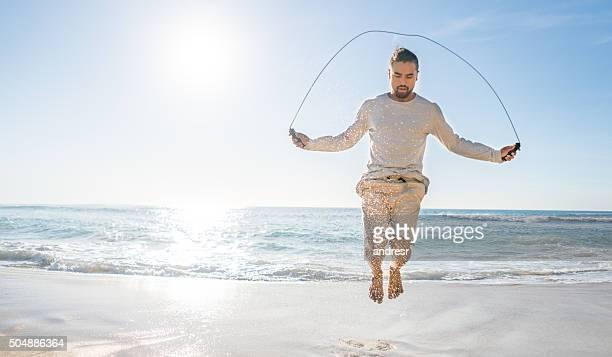Man jumping rope at the beach