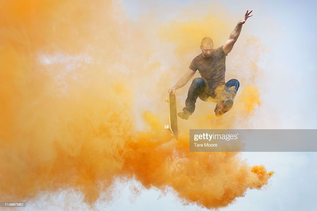man jumping through orange smoke with skateboard : Foto de stock