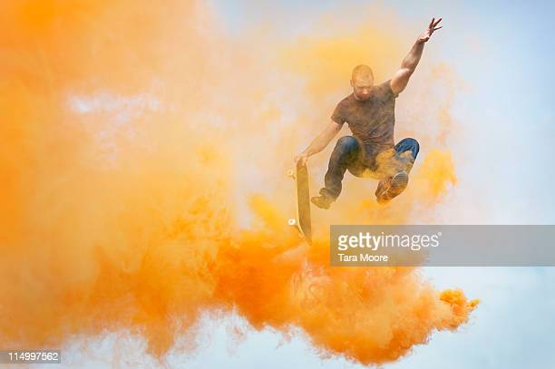 man jumping through orange smoke with skateboard