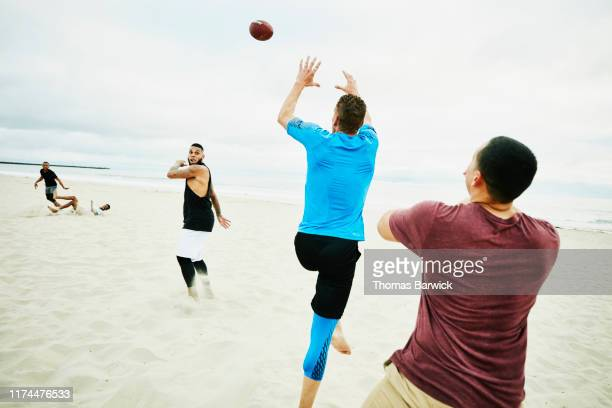 man jumping to catch pass during touch football game on beach - passing sport stock pictures, royalty-free photos & images