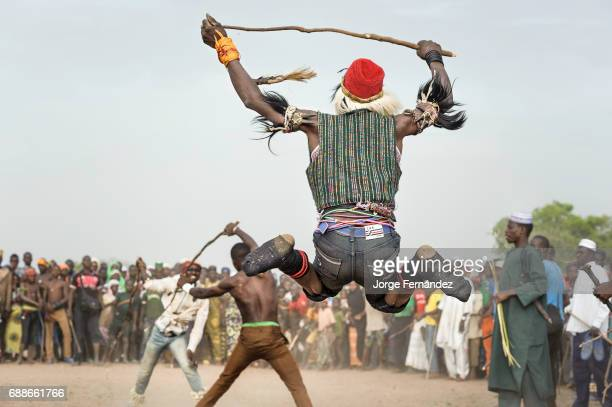 Man jumping to cheer the men who fight with sticks during a rite of passage ceremony in Benin Becoming a man for the Fulani boys of Benin is not an...