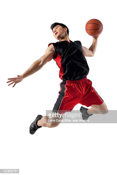man jumping to shoot basketball - ダンクシュート ストックフォトと画像