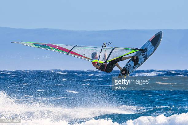man jumping wave on windsurf board - windsurfing stock pictures, royalty-free photos & images