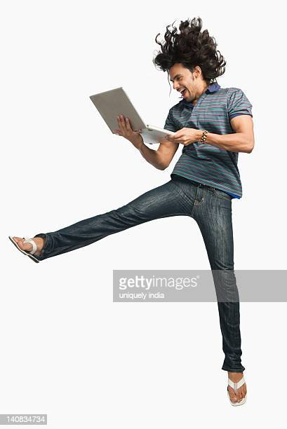 Man jumping while using a laptop