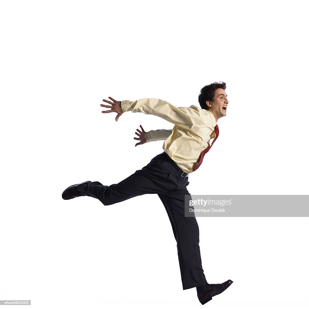 Man jumping with arms behind back : Stockfoto