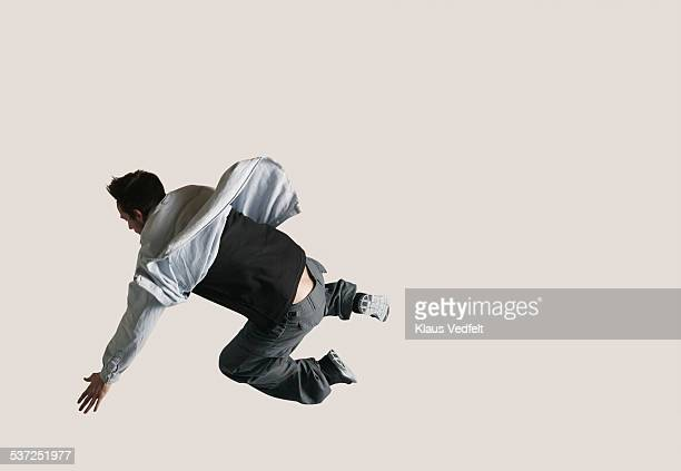 Man jumping with bend legs & back to camera