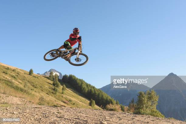 Man jumping with mtb in midair against clear blue sky