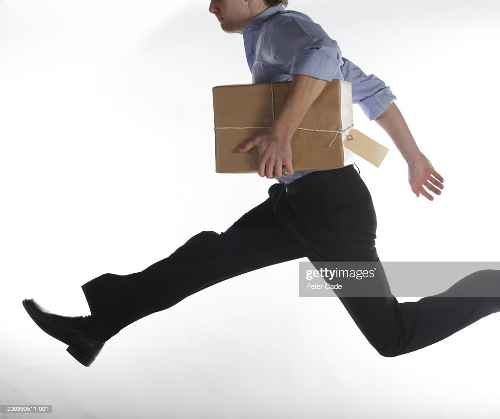 Man jumping with package, side view : Bildbanksbilder