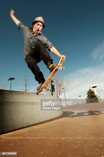 Man jumping with skateboard at park