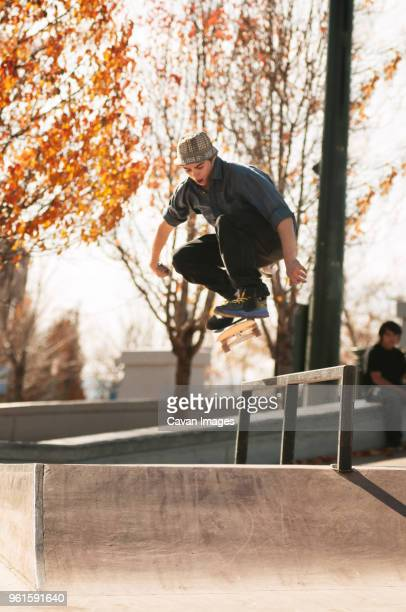 Man jumping with skateboard on sports ramp