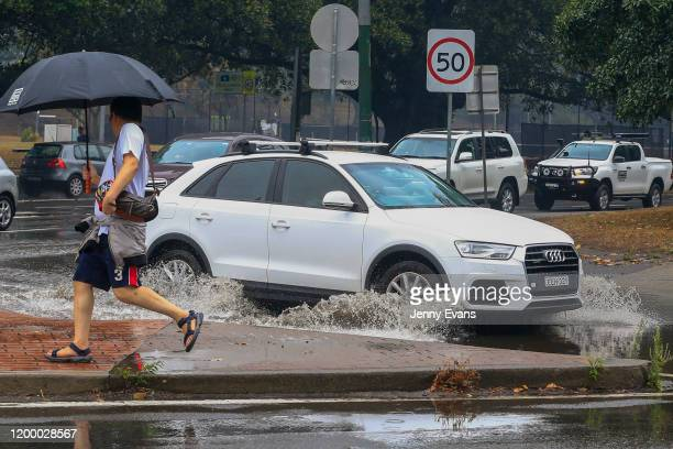 A man jumps away as car is seen traveling through flooded streets in Surry Hills as rain falls on January 17 2020 in Sydney Australia A severe...