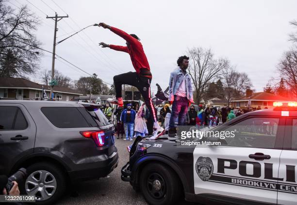 Man jumps between two police cruisers as people confront police on April 11, 2021 in Brooklyn Center, Minnesota. Protesters took to the streets today...