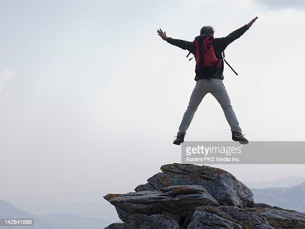 man jumps for joy from rock summit, mtns below - legs apart stock pictures, royalty-free photos & images