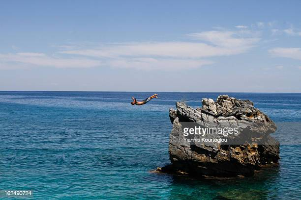 Man jumps from a rock into the sea in Mylopotamos beach in Pelion on August 13,2011