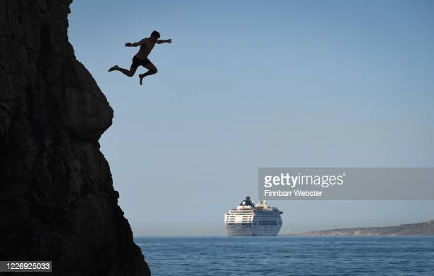 Man jumps from Durdle Door against the backdrop of a cruise ship as tourists enjoy the hot weather at Durdle Door beach on May 25, 2020 in West...