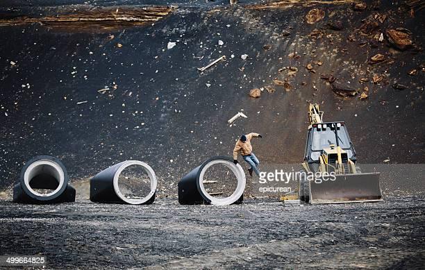 Mann springt von großen pipe in einem industriellen Baustelle