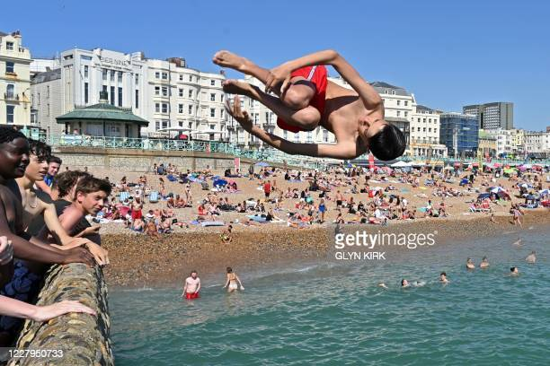 Man jumps from the jetty into the sea in Brighton, on the south coast of England as the temperature is expected to hit 37C on August 7 the second day...