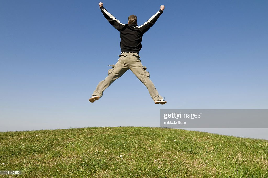 Man jumps high in the air beacuse he is happy : Stock Photo